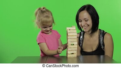 Mother and daughter play. Child pulls wooden blocks from...