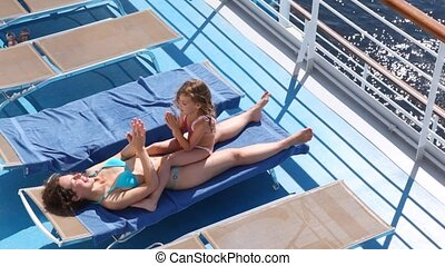 Mother and daughter play in okie dokey lying in chaise lounge