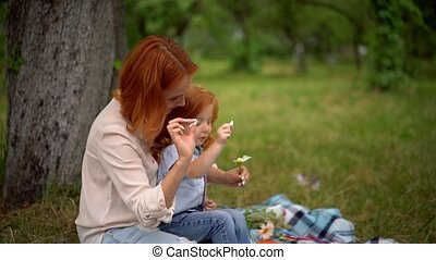 Mother and daughter play with chamomile outdoor - Beautiful...