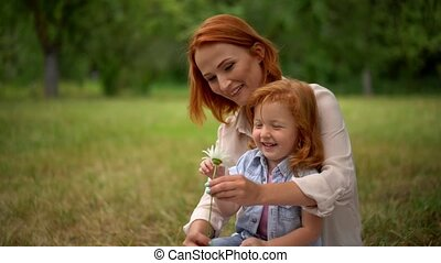 Mother and daughter play with chamomile outdoor