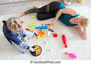 Mother and daughter play with toys on carpet during quarantine due to COVID-19