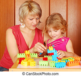 mother and daughter play with toys