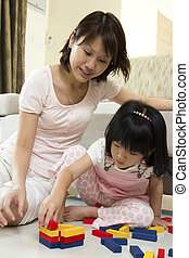 Mother and daughter playing blocks