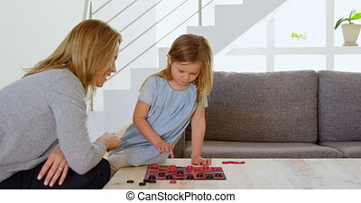 Mother and daughter playing board game on table at home 4k