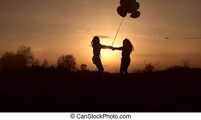 Mother and daughter playing in field at sunset - Silhouettes...