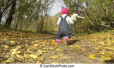 mother and daughter playing in the autumn forest