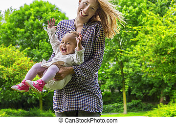 Mother and daughter playing in the park - Cheerful mother...