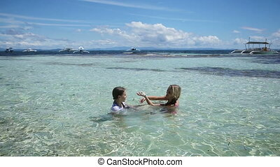 Mother and daughter playing in the tropical sea