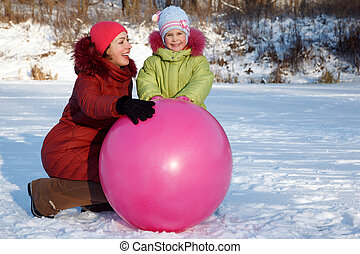 Mother and daughter playing outdoors in winter, with large inflatable ball.
