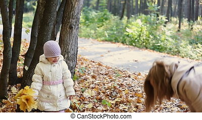 mother and daughter playing together in the autumn park