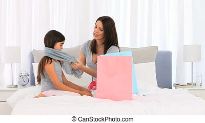 Mother and daughter playing with a scarf on a bed