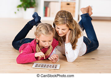 Mother and daughter playing with a tablet - Attractive young...