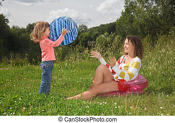 mother and daughter playing with ball in summer day at wood