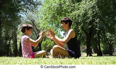 Mother and daughter playing with hands in city park. Happy...