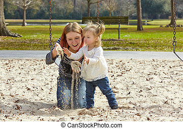 Mother and daughter playing with sand in park