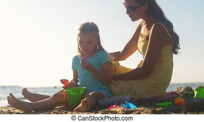 mother and daughter playing with toys on beach