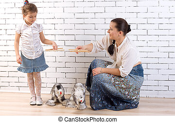 Mother and daughter playing with two toy dogs