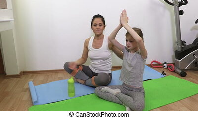 Mother and daughter practicing yoga in living room