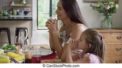 Mother and daughter praying before having meal at dining table 4k