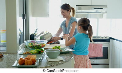 Mother and daughter preparing food in kitchen at home 4k