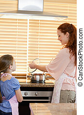 Mother and daughter preparing meal