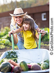 Mother and Child Daughter pushing Wheelbarrow with Harvest