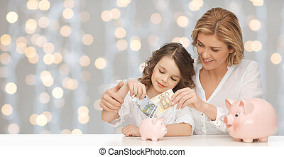 mother and daughter putting money to piggy banks - people, ...