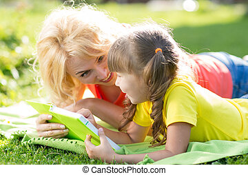 Mother and daughter reading a book at the park