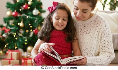 mother and daughter reading book at christmas - christmas,...