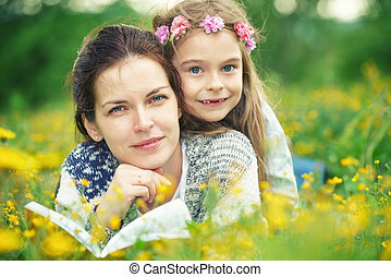 Mother and daughter reading book on green spring meadow