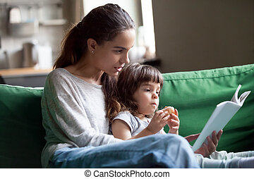 Mother and daughter reading book sitting on sofa at home