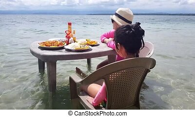 Mother and daughter ready to eat on a table in the beach