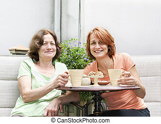 Mother and daughter relaxing in backyard