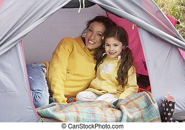 Mother And Daughter Relaxing Inside Tent On Camping Holiday