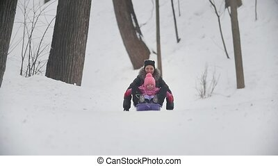 Mother and daughter riding the sledge in winter park