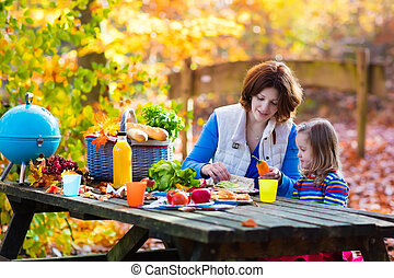 Mother and daughter set table for picnic in autumn