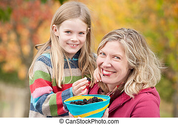 Mother and daughter sharing blackberries