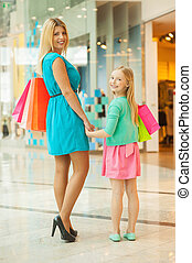 Mother and daughter shopping. Cheerful blond hair mother and daughter holding shopping bags and looking over shoulder while standing in shopping mall