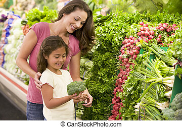 Mother and daughter shopping for fresh produce in...