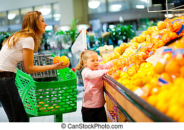 mother and daughter shopping for fruit