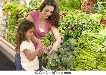 Mother and daughter shopping for produce