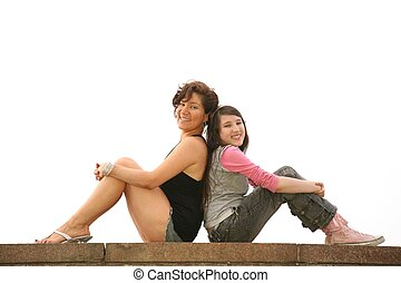 mother and daughter sit on the rock wall