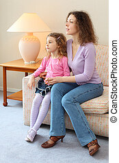 Mother and daughter sits on couch in cozy room, mom says and daughter listens