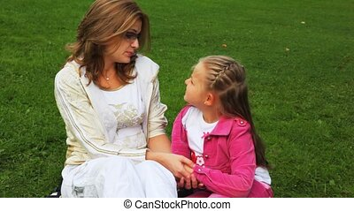 mother and daughter sits on field in park and talk