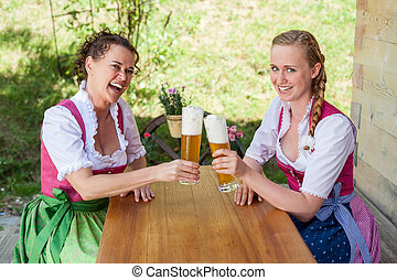 Mother and daughter sitting at a table in dirndl in front of a glass of beer.