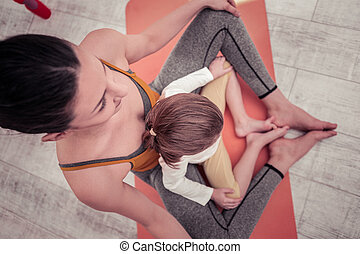 Mother and daughter sitting in a butterfly pose