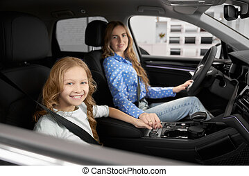Mother and daughter sitting in front seats of new auto.