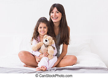 Mother and daughter sitting on bed with teddy bear