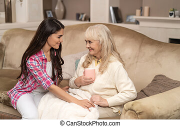 Mother and daughter sitting on couch together.
