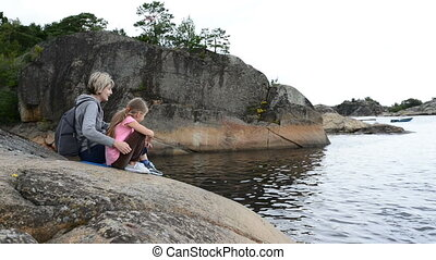 Mother and daughter sitting on the big stones on the sea shore